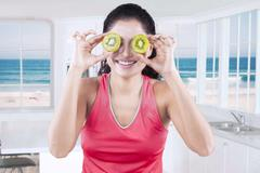 Female model with two slices of fresh kiwi - stock photo