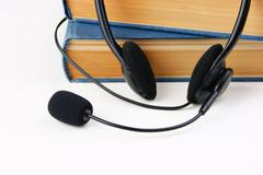 Headphones with a microphone and a stack of books - stock photo