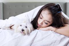 Lovely woman sleeping with puppy on bed - stock photo