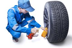 Male mechanic clear up a wheel - stock photo