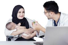 Mother and her baby get drugs from doctor - stock photo