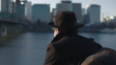 Man in suit, shades and hat looking out at the city. Camera revolves around him Stock Footage