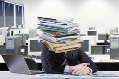Overworked entrepreneur with a paperwork pile - stock photo