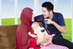 Parents arguing while carrying their baby - stock photo