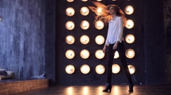 Beautiful girl dances against lamps Stock Footage