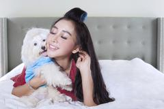 Pretty model and her puppy on bed - stock photo
