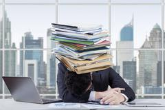 Stressed worker with a paperwork stack - stock photo
