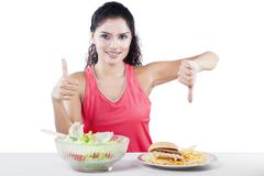 Woman Choosing Between Salad And Junk Food Stock Photos