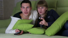 Frightened young couple with glass of wine watching the horrors on television - stock footage