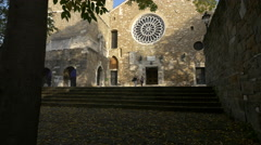 Two people walking in front of Cattedrale di San Giusto Martire, Trieste Stock Footage