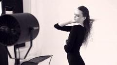Beautiful model dances in front of the fan Stock Footage