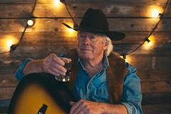 Country and western musician sitting with guitar. Having a drink. - stock photo