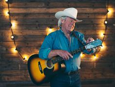 Senior country and western musician tuning his guitar. - stock photo