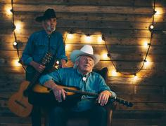Two smiling senior country and western musicians sitting on chair in front of - stock photo