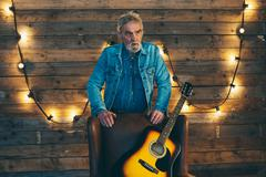 Senior musician with beard leaning on back of chair with acoustic guitar. - stock photo