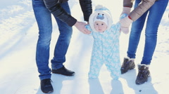 A happy family. Mother and father teaches a child to walk in winter park Stock Footage