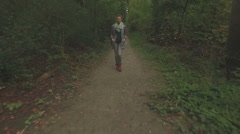 Aerial of a young woman walking through a forest, low altitude tracking shot Stock Footage