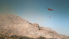 Fire fighting chopper douses flames Stock Footage