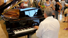 A white man playing the piano in the mall - stock footage