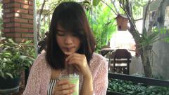 Woman drink green tea frappe with tube in glass cup. Stock Footage