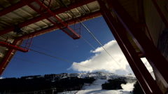 Cableway station and snowy mountains in a sunny day - stock footage