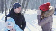 Father and mother walk in park with child at winter slowmotion Stock Footage
