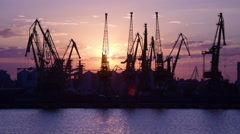 Purple sunset and Cranes of Odessa trading port, zoom out, industrial background - stock footage