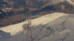 On a cableway with valley and snowy mountains in the background Stock Footage