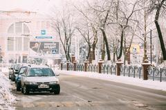 Cars parking in the avenue of Victory in Gomel. Snowy street in - stock photo