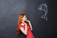 Cute afraid woman scared of shark drawn on chalkboard background Stock Photos