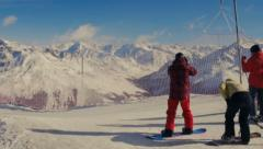 Skiers and snowboarders and snowy mountains Stock Footage