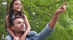 Handsome father giving piggy back to his daughter and showing something Stock Footage