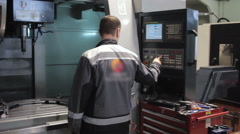 Male Engineer Operating CNC Machinery On Factory Floor Stock Footage