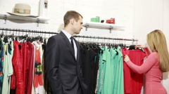 A man waits for his woman chooses a dress in a store. nervous and takes the Stock Footage