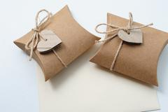 Two Small Handmade gift boxes with kraft paper with heart on white - stock photo