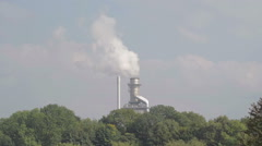 A shot of heavy industry with air pollution set in a pretty rural location. Stock Footage