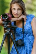Calm young woman with camera on tripod Stock Photos