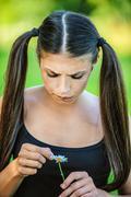 Woman wonders, tearing petals on daisy Stock Photos