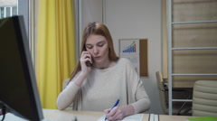 Busy woman talking on the phone and making notes on a sheet of paper. Stock Footage