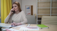 Woman takes a call at the workplace. - stock footage
