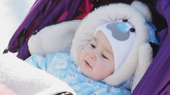 Portrait of cute baby in pram at winter - stock footage