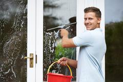 Portrait Of Man Cleaning House Windows Stock Photos