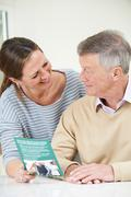 Senior Man With Adult Daughter Looking At Brochure For Retirement Home - stock photo