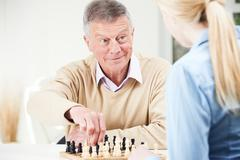 Senior Man Playing Chess With Teenage Granddaughter Stock Photos