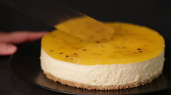 An adult cuts a passionfruit cheesecake in a close view - stock footage