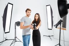 Stock Photo of Model and photographer standing in studio