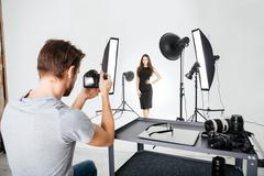 Man shooting female model in studio - stock photo
