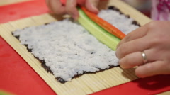 A woman prepares sushi rolls with a bamboo mat Stock Footage