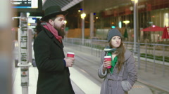 Young couple chat and flirt while waiting for train at a station downtown, night - stock footage