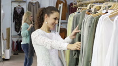 Happy young girls choosing new clothes in shop Stock Footage
